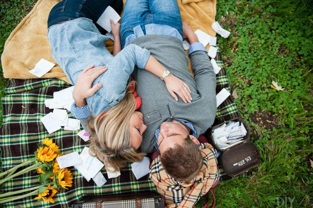 Surrounded by love letters in an engagement photo shoot