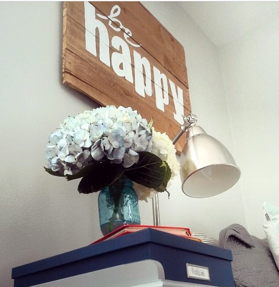 Be Happy pallet sign hanging on the wall above a nightstand