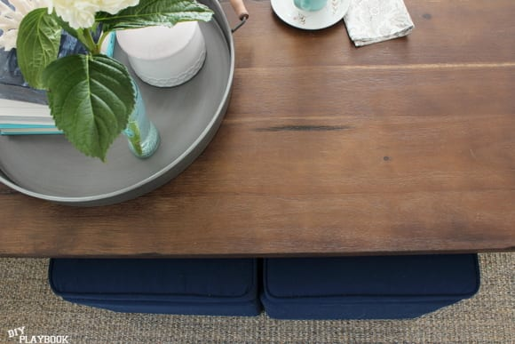 This dark wooden coffee table pairs well with the blue stools.
