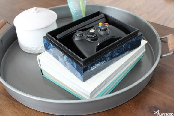 A coffee table tray is a smart way to store video game controllers.
