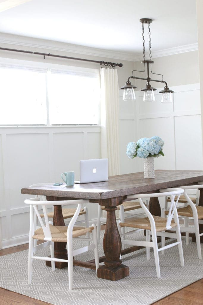 Rustic dining room table with white wooden chairs and hanging light fixture.