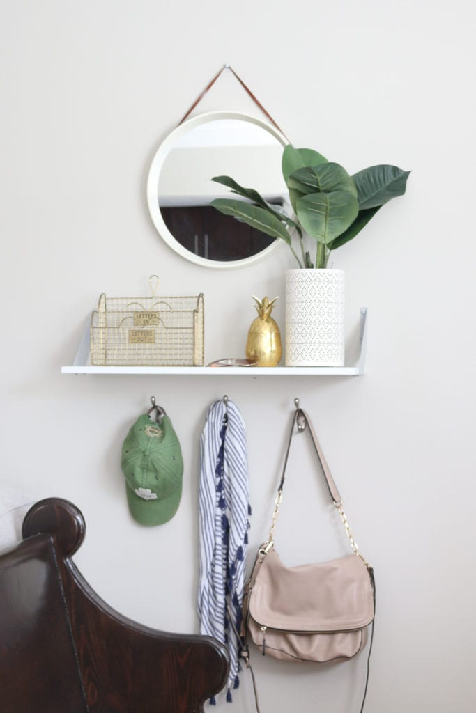 The entryway of Bridget's small home is both perfectly styled and totally functional with hooks, a bench and even some greenery.
