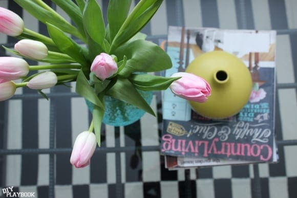 The blue vase with pink tulips pairs well on a glass coffee table.