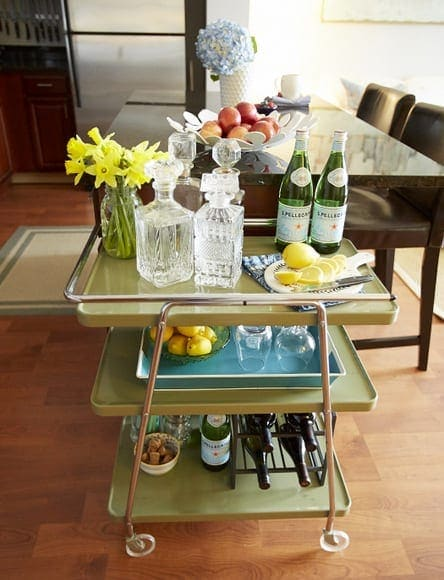 This vintage bar cart with crystal bottles and fresh flowers adds to the entire space.