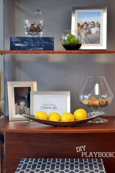 This modern book shelf decorated with photos and other accessories is industrial.