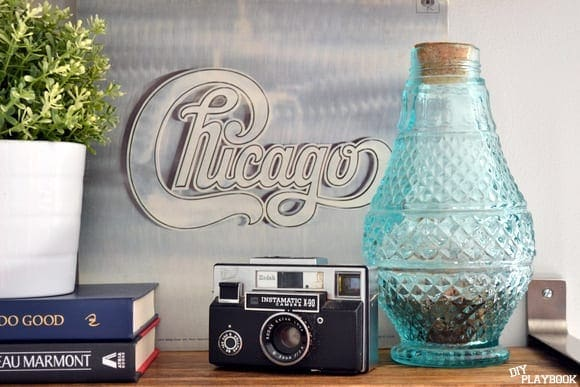 The blue vase as a coin collector ads a vintage touch to this Chicago themed book shelf.