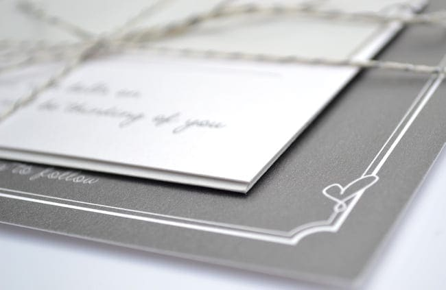 A simple cursive heart on the corner of the wedding invitations