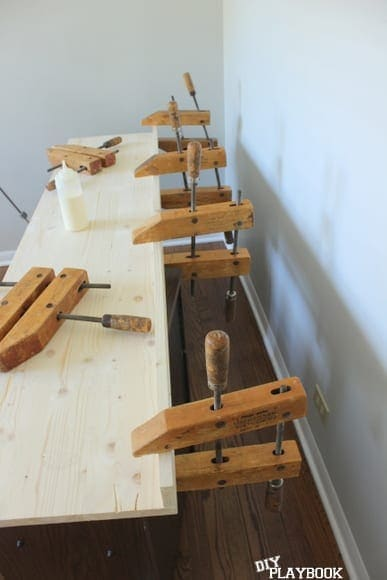 Using wood clamps to hold the desk as it dries.