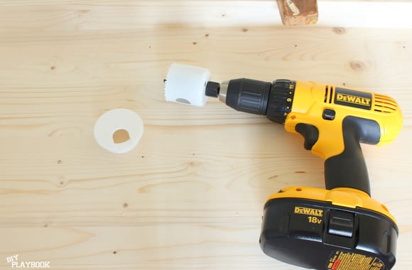 Using a Dewalt drill to make holes in the desk for cords.