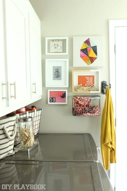 This gallery wall in the laundry room is colorful and interesting.