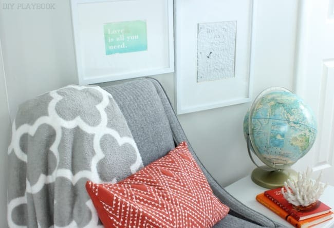 This gray chair pairs well with the coral pillow and cozy blanket.
