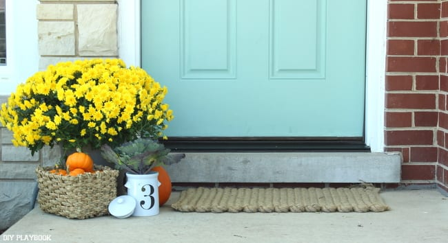 This turquoise front door surrounded by fresh flowers and pumpkins is festive for fall.