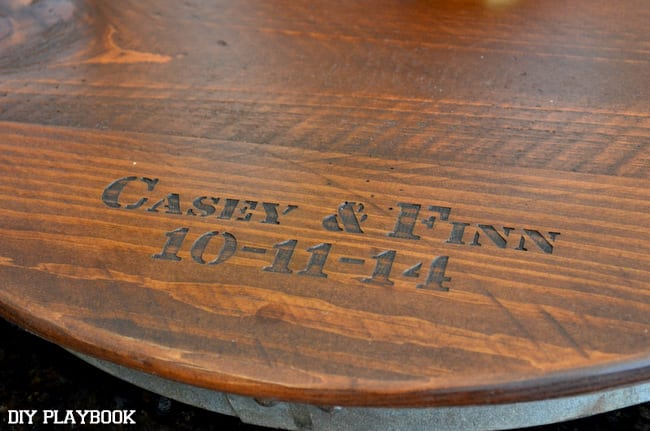 This personalized lazy susan is stained dark with an industrial silver accent.