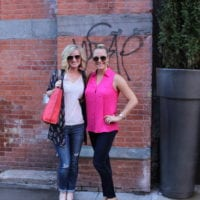 Bridget and Casey snap a pic in front of a rustic NYC brick wall.