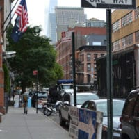 This NYC block features an American flag and street sign.
