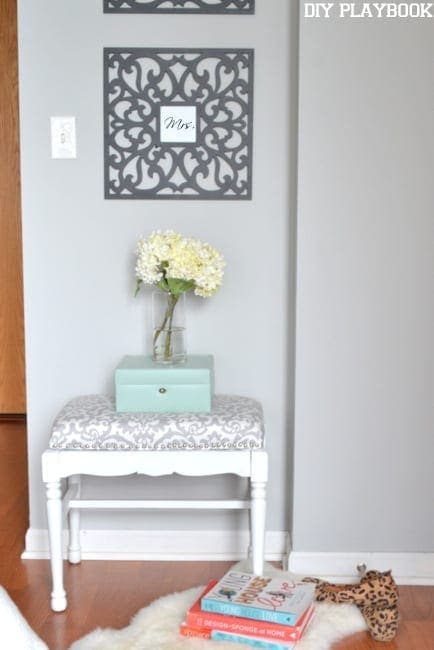 This corner nook is adorable with a textured stool and fresh flowers in a vase.