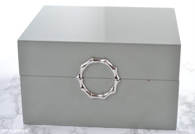 Grey decorative box with a silver clasp on the front.