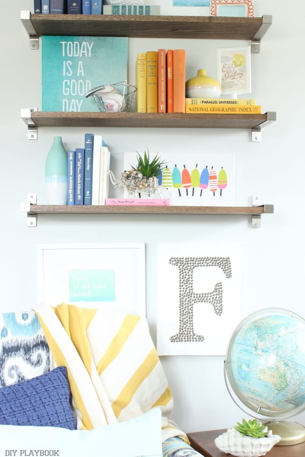 These built in shelves feature fun pieces of wall art, pops of color, and various decor items.
