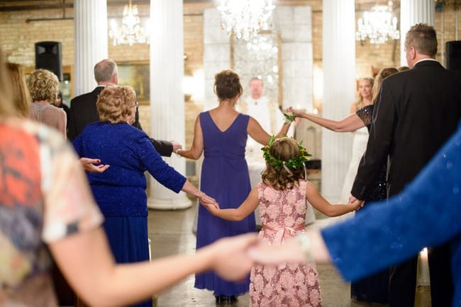 Families gather hands to celebrate the marriage of their loved ones.