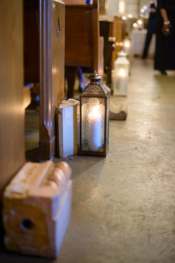These candle lanterns along the aisle add a whimsical element to the wedding.