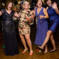 These wedding guests are dancing and having fun.