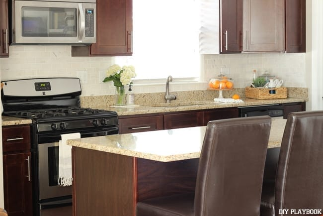 The white backslash in this kitchen pairs well with the tan granite counter tops.