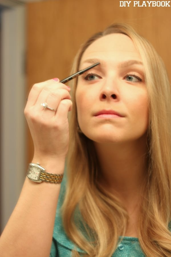 Casey fills in her eyebrows in front of a mirror