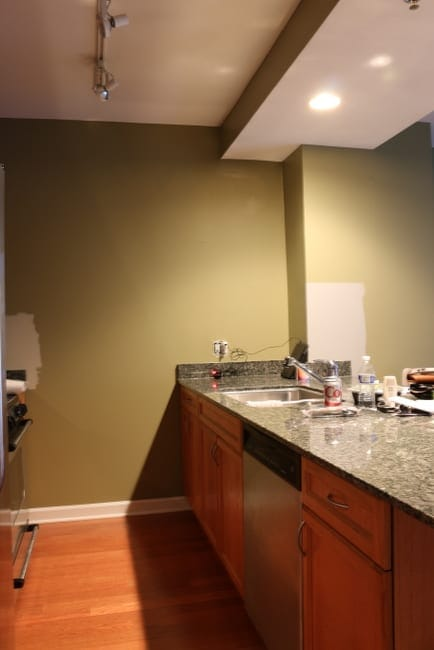 Maggie's kitchen before the makeover. The layout is great, but the weird green wall color definitely has to go.