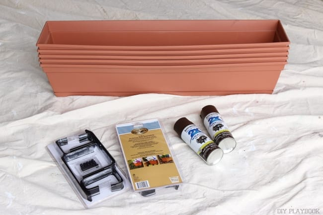 Assemble your materials for the flower boxes: plastic hardware store boxes, brackets, concrete anchors, and brown spray paint.