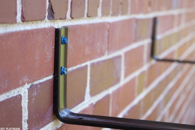 Attach the concrete screws and brackets to the outside brick wall.