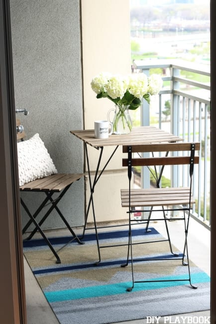 Maggie's balcony is effortlessly chic with this modern bistro table and gorgeous rug.