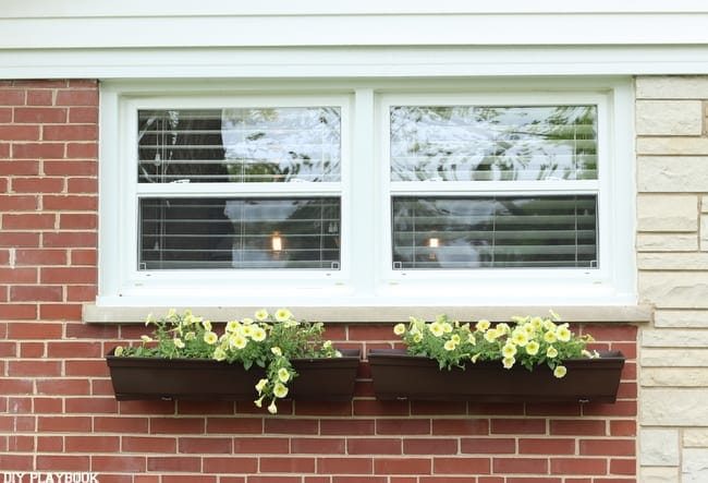 These DIY fake wood flower boxes add character to the home's exterior.
