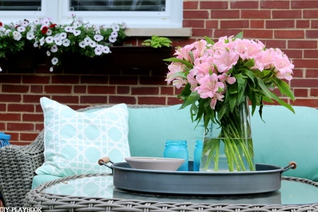 The fresh flowers on this outside coffee table add a pop of color.