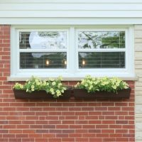These fake wood flower boxes compliment the home's window treatments.