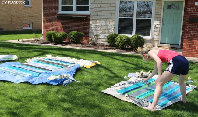 DIY Outdoor Painted Rug - painting in progress! Here's Bridget pray painting our outoor rugs.