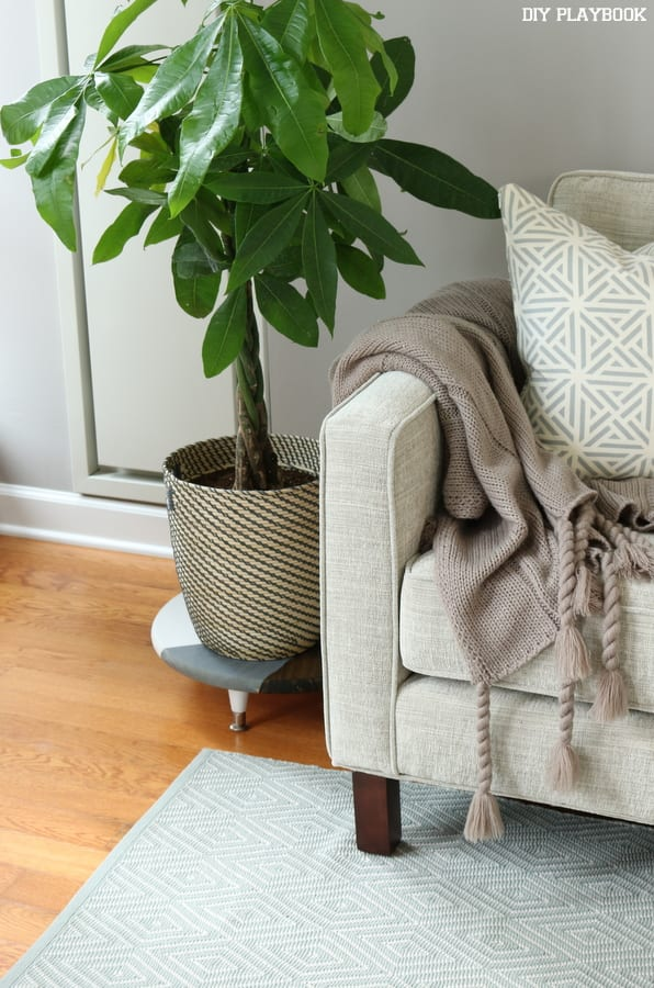This chic plant stand matches the decor of the room.