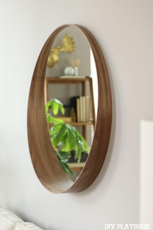 A round mirror on a soft grey wall looks great in this condo revamp.