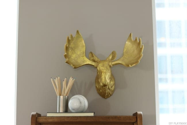 Fun golden moose head adds personality to this grey wall and condo update.