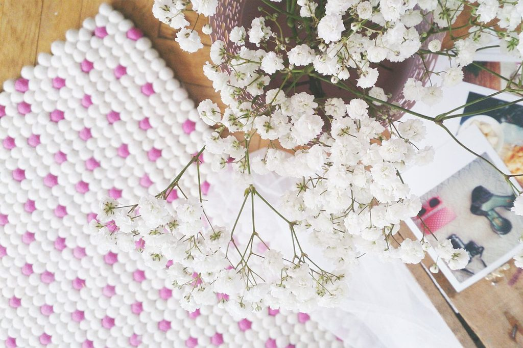 this white and pink polka dot felt ball rug is bright and pretty