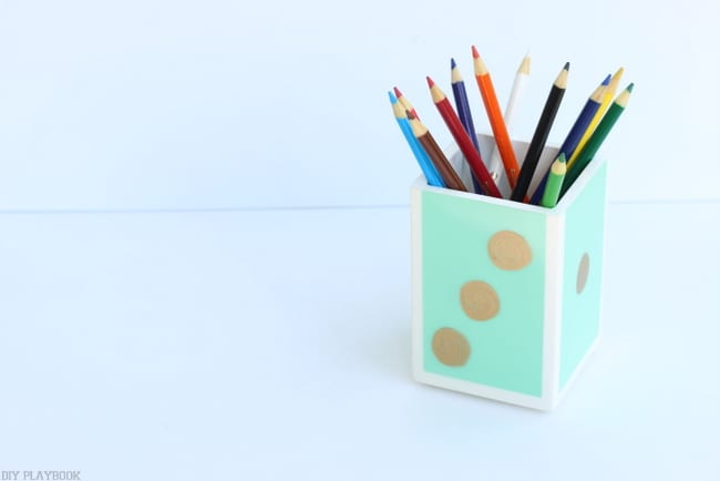 Recreate the face of a die on this simple pencil holder with a gold paint marker
