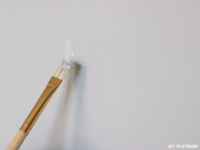 Touch up the paint over the nail hole in the wall with a small detailing paint brush.