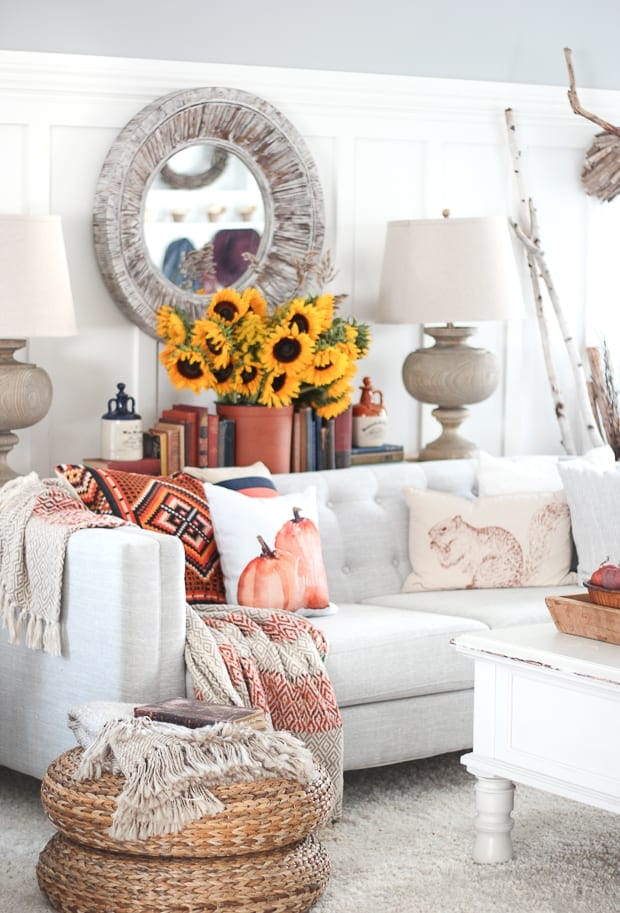 these adorable fall themed throw pillows and bright sunflowers give this room much needed pops of color