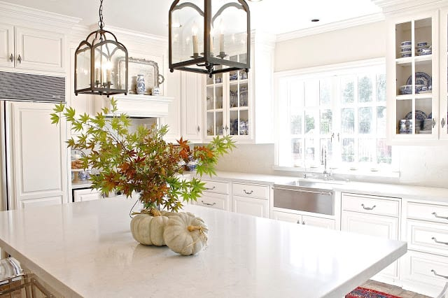 this gorgeous bright kitchen has the simple fall touch of pumpkins and fall leaf bouquet