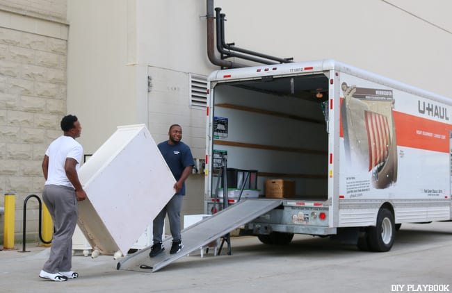 Movers work together to load a dresser into the U-Haul.