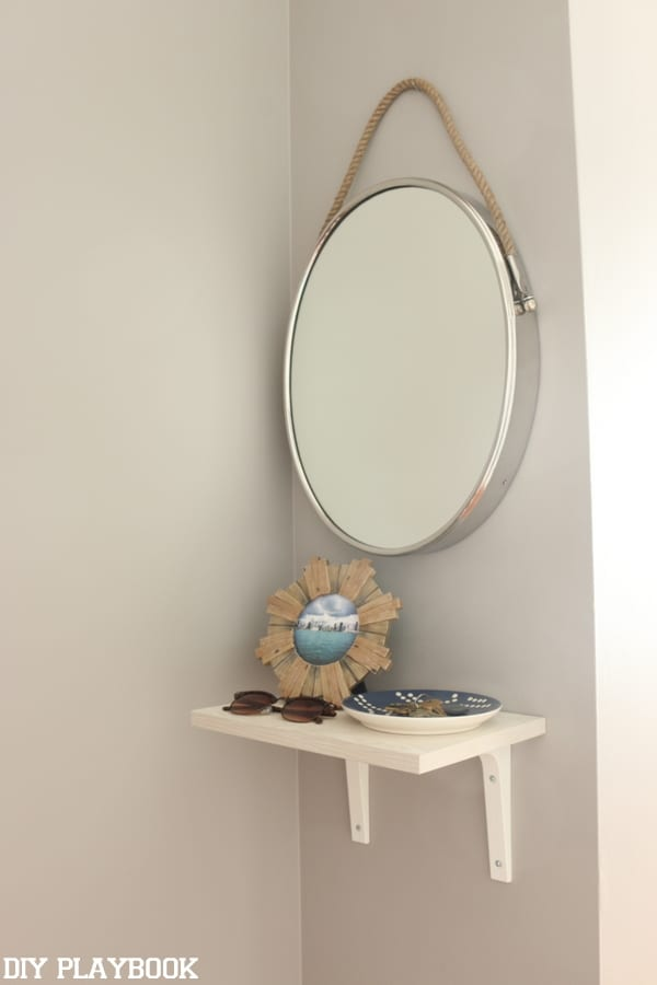 The addition of a simple round mirror and shelf really take the space up a notch!