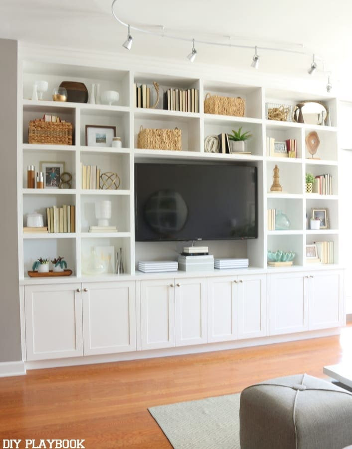 Built-in bookshelf and entertainment center styled with thrifted home accessories.