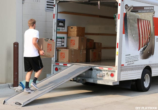 Casey's husband loads a box onto the U-Haul.