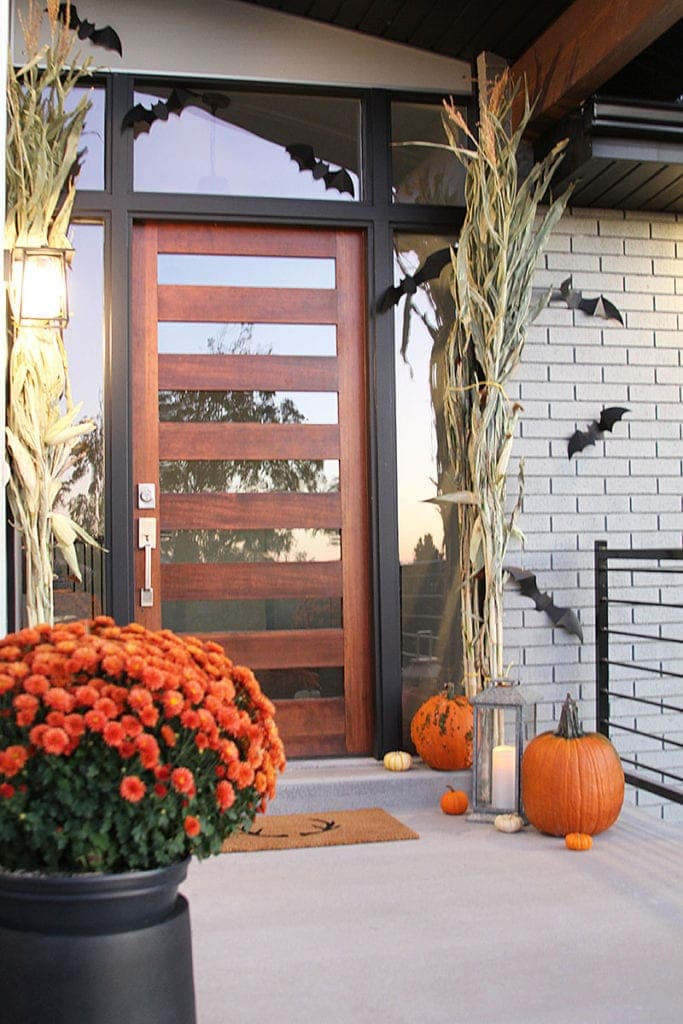 bright pops of orange from the pumpkins and flowers make this a perfect fall front porch