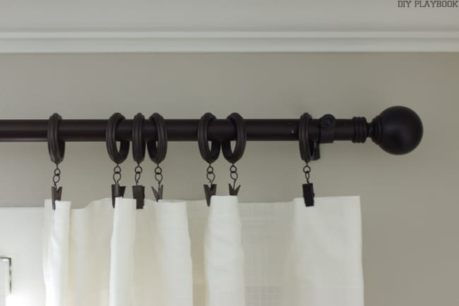 Curtain rod with brown rings and a cream colored curtain.