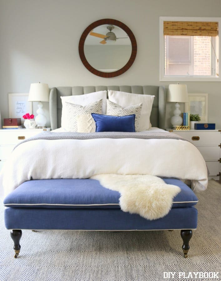 Master bedroom with bright blue accents against a grey and white bed.